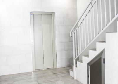 Reforma integral de acceso a viviendas en Romo, Las Arenas. Bajada a cota cero de ascensor y renovación completa del portal.